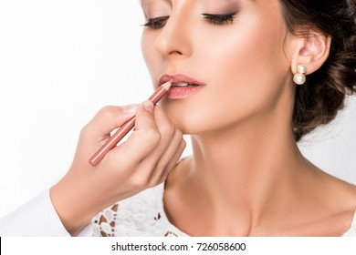 close up view of makeup artist applying makeup using lip pencil isolated on white