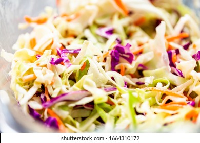 Close up view. Making homemade coleslaw in a glass bowl.