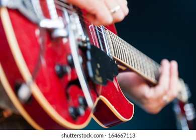 Close up view of a male guitarist playing an electric guitar with focus to the pickup of the guitar and the strings
