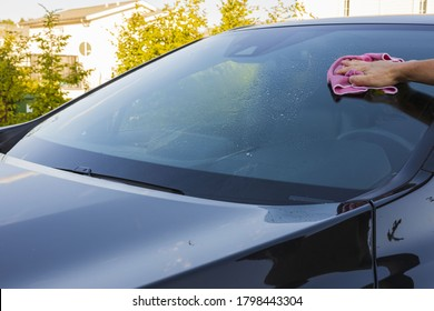 Close up view of male hand cleaning windshield. Vehicle concept background.
