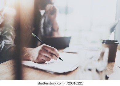 Close up view of male hand holding pencil and making notes notebook.Coworker at working process.Horizontal.Blurred background.Flares