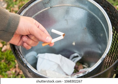 Close up view of male hand throwing broken cigarette in trash can. Stop smoking and healthy life concept.