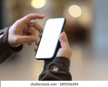 Close up view of male hands touching smartphone include clipping path in blurred background