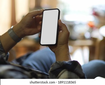 Close up view of male hands using smartphone include clipping path in living room