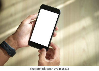 Close up view of male hands using smart phone with modern office blurred background. Blank screen monitor for graphic display montage.
