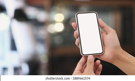 Close up view of man hands holding mock up smart phone with modern cafe blurred background.