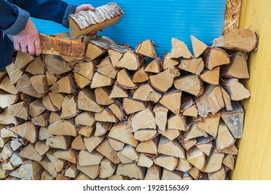 Close up view of a man putting firewood in a woodpile.