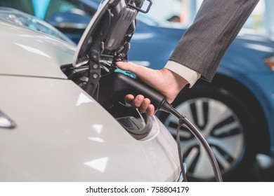 Close up view of man recharging electric car. Mans hand plugging out power cord to electric car.