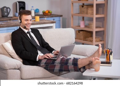Close up view of a man working on freelance at home. Male in jacket and pyjamas trousers on couch with laptop on his knees,