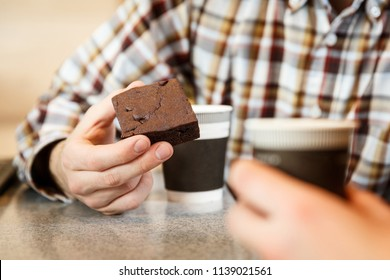Close up view man's hand holding brownie cake while drinking coffee