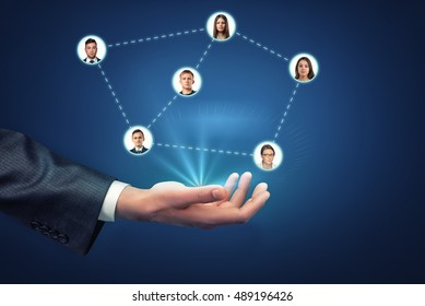 Close up view of a man's hand holding social network userpics connected by dotted lines. Social media. Office staff. Business and professional contacts.