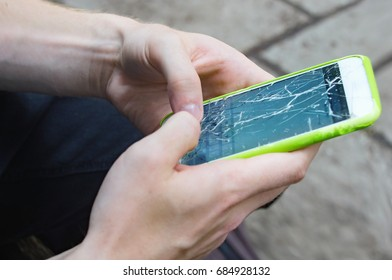 Close view of man's hands with a green mobile phone whose screen is cracked