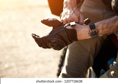 Close view of man's hands while he put on a leather glove to drive a bike.