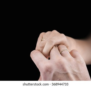 Close view of man's and woman's hands with wedding rings in a black background