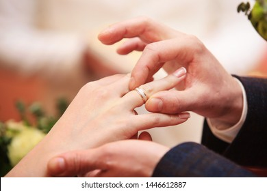 Close up view at a mans's hand putting wedding ring on a woman ring finger. Wedding concept