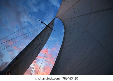 Close up view of the mast and grotto and sails against purple sunset