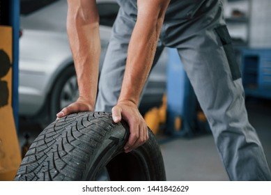 Close up view. Mechanic holds a tire at the repair garage. Replacement of winter and summer tires.