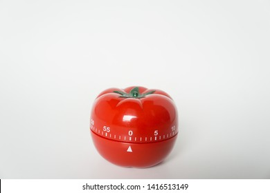 Close up view of mechanical tomato shaped kitchen clock timer for cooking and studying. Used for pomodoro technique for time & productivity management. Isolated on white background, set at 0 minutes.