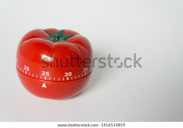 Close up view of mechanical tomato shaped kitchen clock timer for cooking and studying. Used for pomodoro technique for time & productivity management. Isolated on white background, set at 25 minutes.