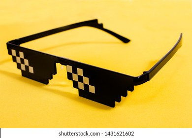 Close up view of meme pixel glasses isolated on a yellow background.