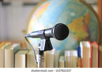 A close up view of a microphone in the classroom Rows of books and globes as background selective focus and shallow depth of field