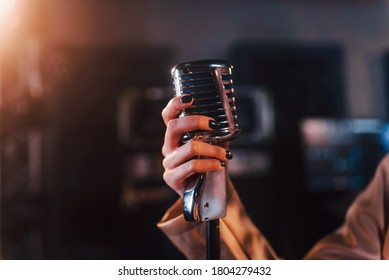 Close up view of microphone. Young beautiful female performer rehearsing in a recording studio.