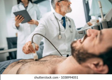 Close up view of mid adult man undergoing ultrasound scan in modern clinic. Man doing neck ultrasound examination at hospital. Focus on hand.