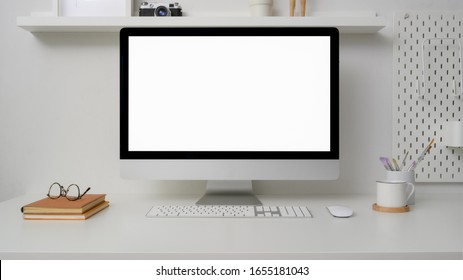 Close up view of minimal workspace with blank screen computer, office supplies and decorations on white desk with shelf on white wall