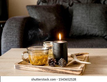 Close up view of minimalist Scandinavian style black color details home decor concept. Wood tray with steaming herbal tea, illuminated black candle, deer antler, pine cones.