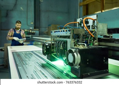 Close up view of modern laser engraving equipment in industrial workshop, machine processing glass with unrecognizable operator in background, copy space