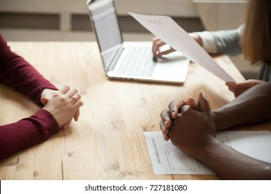 Close up view of multiethnic HR team discussing job applicants resume. African american holds hands over employment agreement, female holding candidates CV. Job interview with human resources concept.