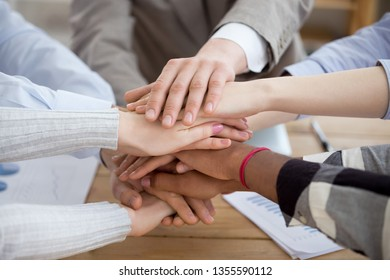 Close up view multiracial people putting hands together, high five. Stack of hands. Multiethnic group of young millennial business workers. Team work, team building, unity, friendship, support concept