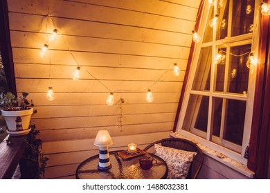 Close up view of nautical theme home balcony at night with string light bulbs.