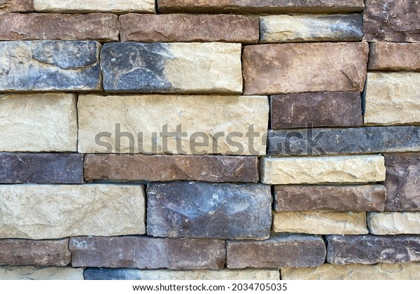a close up view of new stone block structure building wall dark and light color cut stones