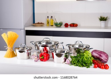 close up view of nice cookware set with some vegetables on kitchen in back