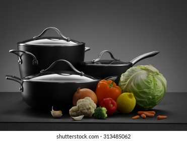 close up view of nice cookware set with some vegetables on grey color back