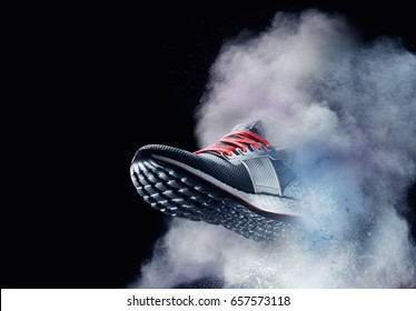 close up view of nice sport shoe is getting out of dusty cloud