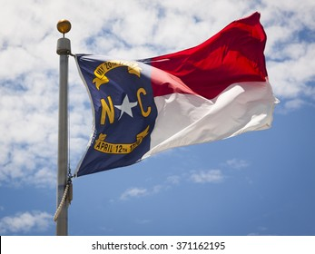 Close up view of the North Carolina flag waving in the wind in the afternoon.