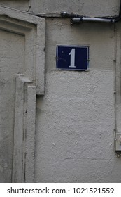 Close up view of the number one written on a blue rectangle fixed on the wall of an old house. Decorative elements and lines on the beige painted wall. Numeric white symbol in a city street in France