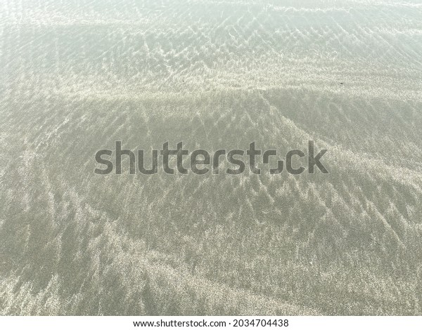 a close up view of ocean beach sand ripples wave pattern low tide effect