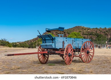 Close up view of old blue chuck wagon with red wheels and dark blue buck board with deep blue sky