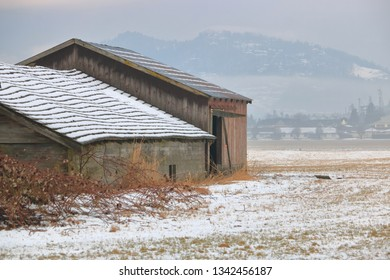 Close view of old farm buildings sprinkled with a dusting of snow during the early Canadian Spring season.