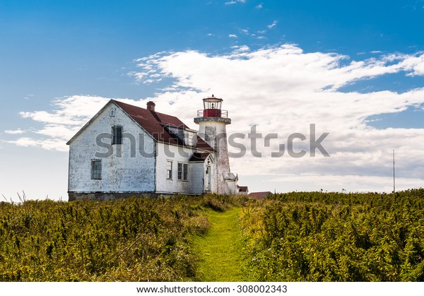 close view of old lighthouse and guardian house  in Longue-Pointe-de-Mingan, Quebec, Canada
