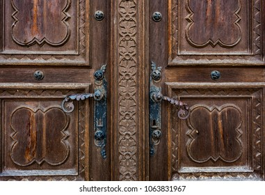 Close up view of an old, massive, wooden, door with decorative carvings and with cast iron decorations and door handles. Saint Peters Cathedral main door in city of Djakovo in Slavonia, Croatia