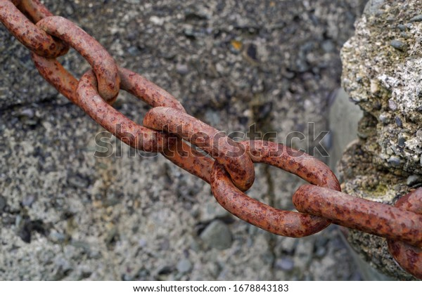 A close up view of the old, rusty chain link, with weathered concrete blocks in the background.