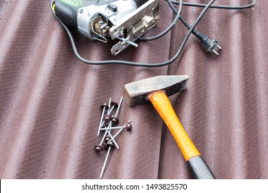 Close up view on asphalt roofing shingles background with hammer and nails.