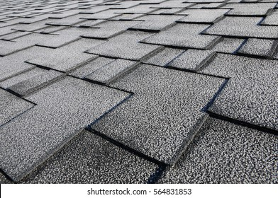 Close up view on asphalt roofing shingles covered with frost