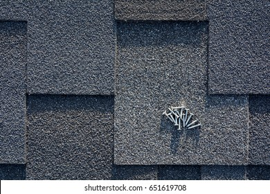Close up view on asphalt roofing shingles and nails background.