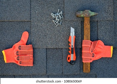 Close up view on asphalt shingles on a roof  with hammer,nails and stationery knife. Use of gloves in construction