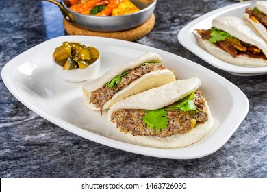 Close up view on bao with beef cheek. Gua bao, steamed buns served on white plate. Taiwan's traditional food Gua Bao on marble table. Asian sandwich steamed. Asian fast food